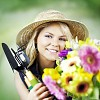 Smiling gardener holding gardening tools and colorful flowers