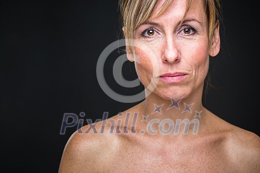 Portrait of a smiling middle aged caucasian woman against dark background - radiating confidence and feminity (shallow DOF; color toned image)
