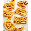 Tasty fresh homemade puff pastry with peach and honey on the white wooden table.